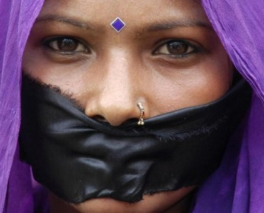 Woman with her mouth covered with black cloth takes part in a silent protest against the government in Jammu