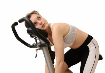 Isolated tired young woman siting on spinning bicycle