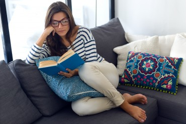 Portrait of beautiful young woman reading a book on the sofa.