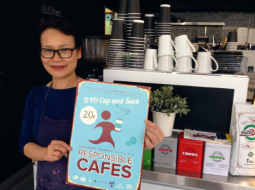 Cafe owner holding up BYO sign