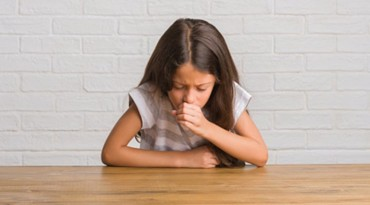Young hispanic kid sitting on the table at home feeling unwell and coughing as symptom for cold or bronchitis. Healthcare concept.