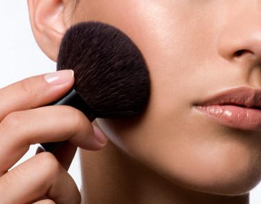 woman applying rough on cheek