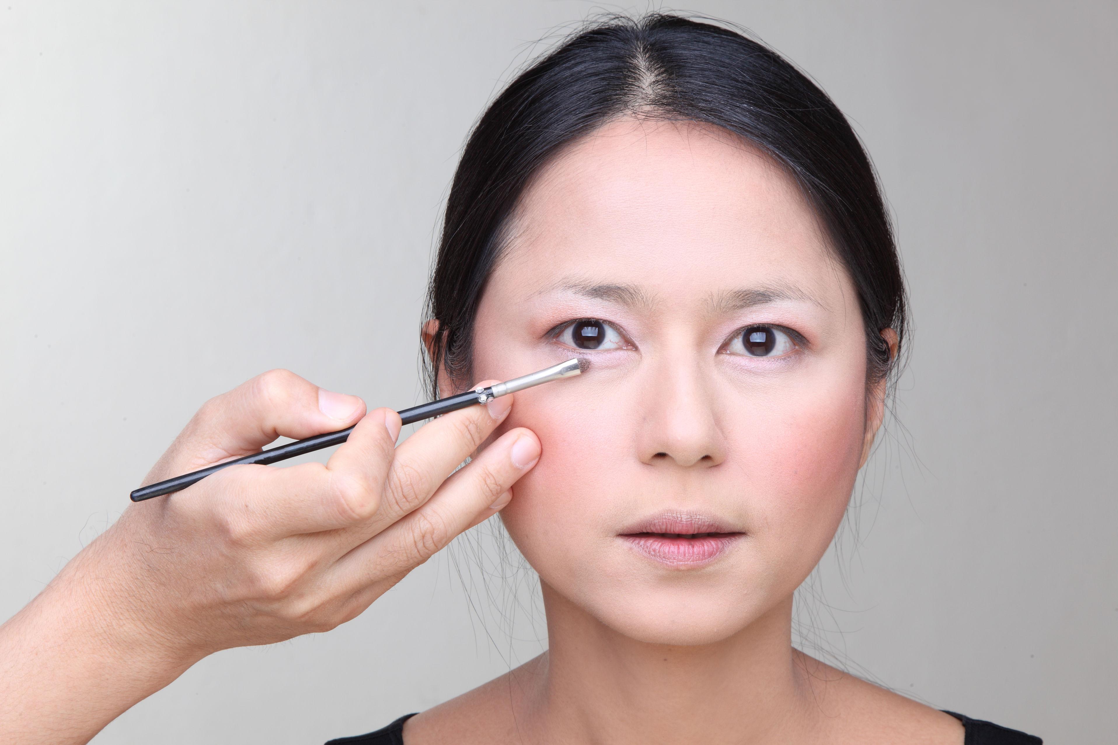 girl applying eye liner