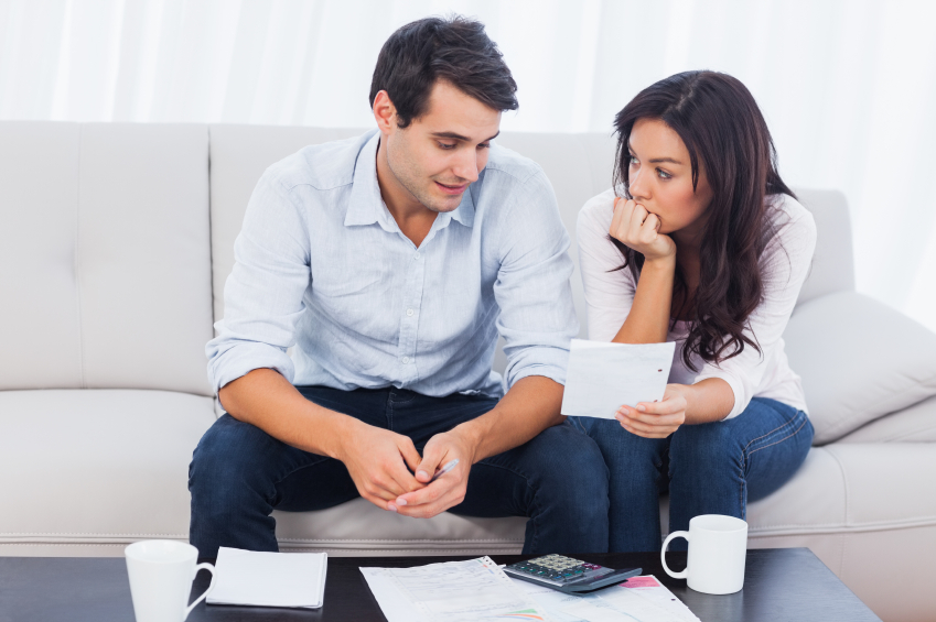 Fearful young couple doing their accounts sat on a couch