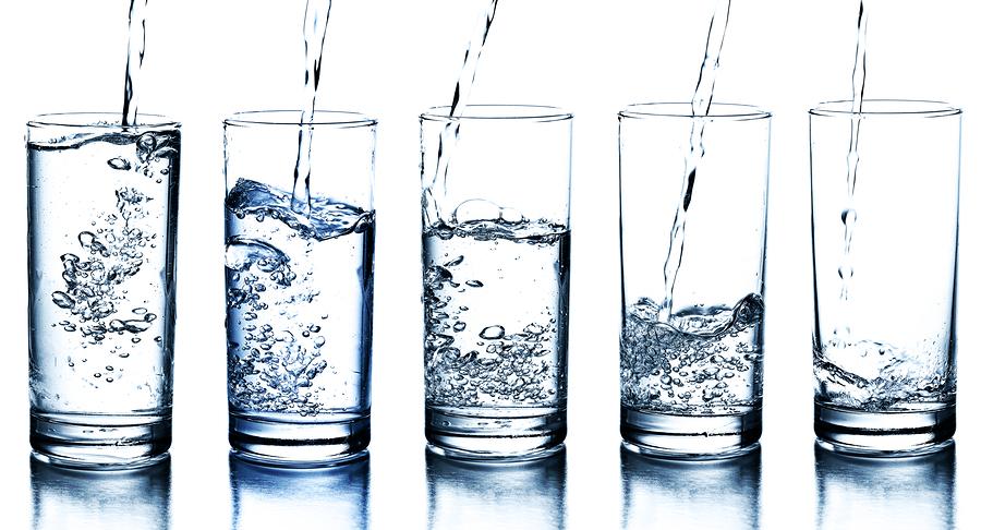 five water glasses being filled in descending order