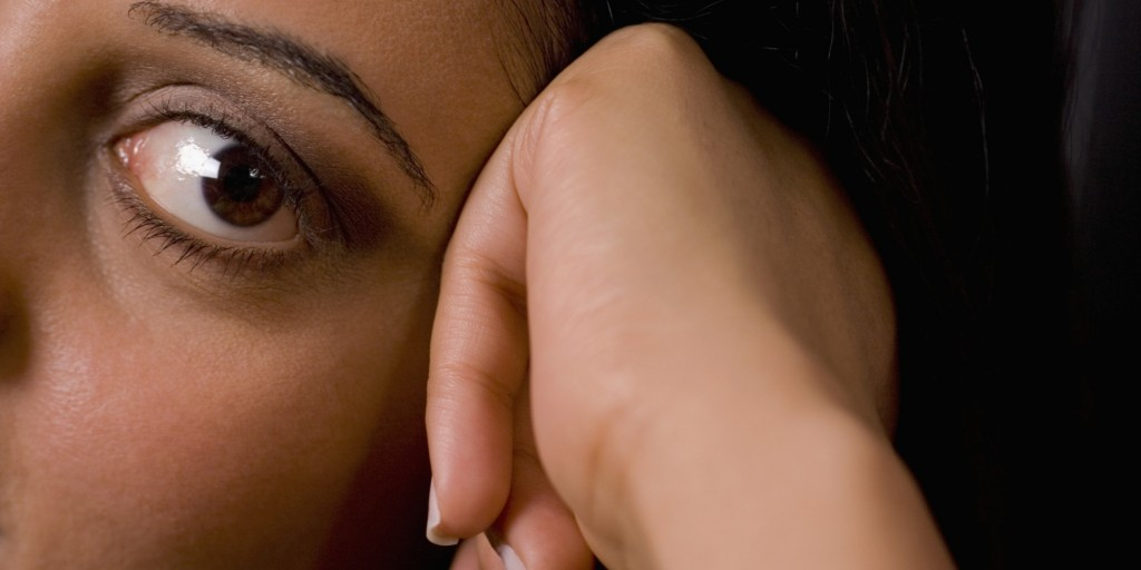 Close-up of a young woman resting her head on her hand