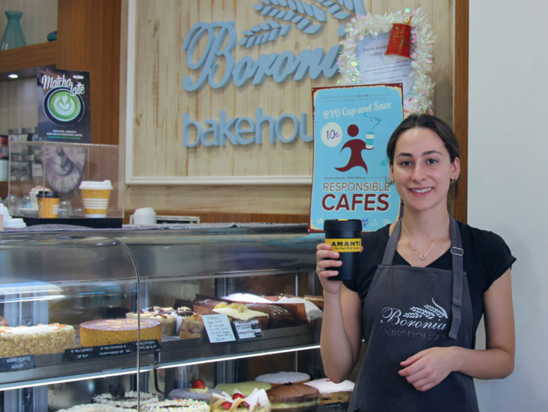 Bakery owner displaying BYO sign